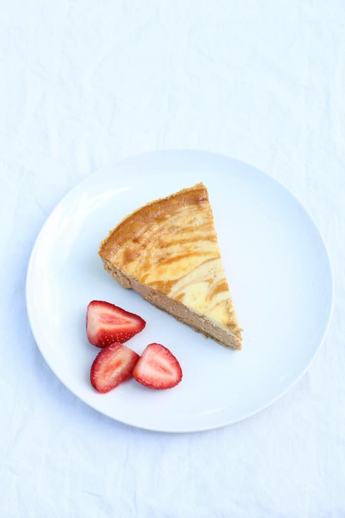 slice of easy pumpkin cheesecake recipe on a white plate with fruit
