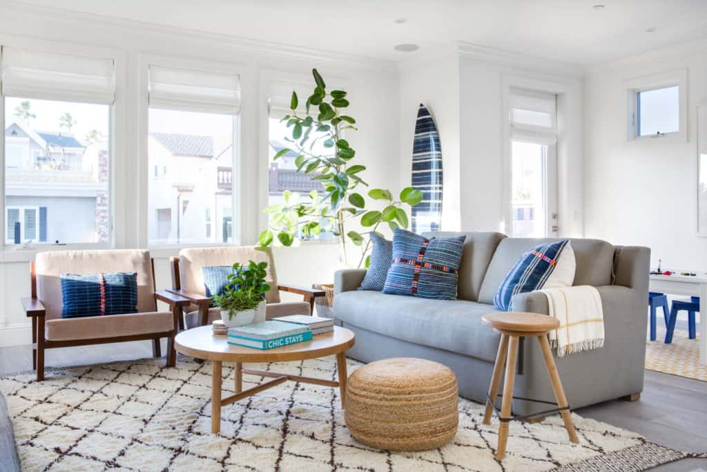 Textured accessories in pillows, ottomans and books in this beach home