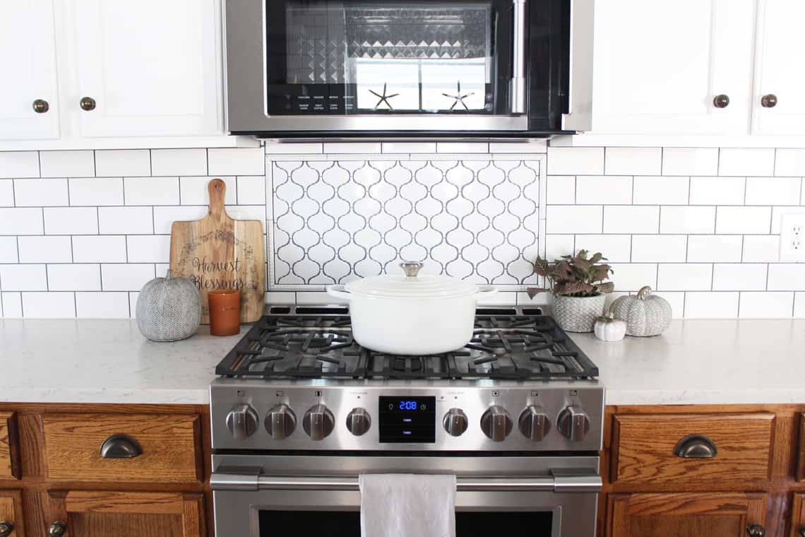 Cozy Fall Decorating Ideas. Kitchen stove with a fall vignette on either side with a le creuset dutch oven on top of the stove.