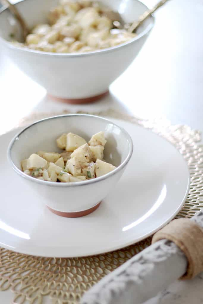 place setting with potato salad in an individual bowl and a serving bowl