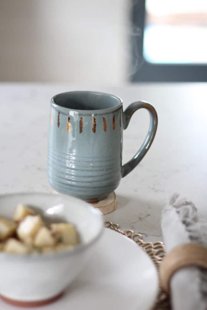 mug of apple cider and bowl of potato salad on a countertop